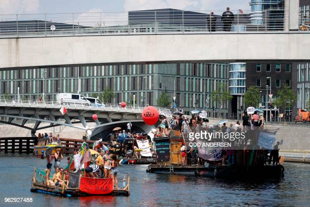 Counterdemonstrators drive on the Spree with boats and rafts passing by the Reichstag building housing the Bundestag in the direction of the main...