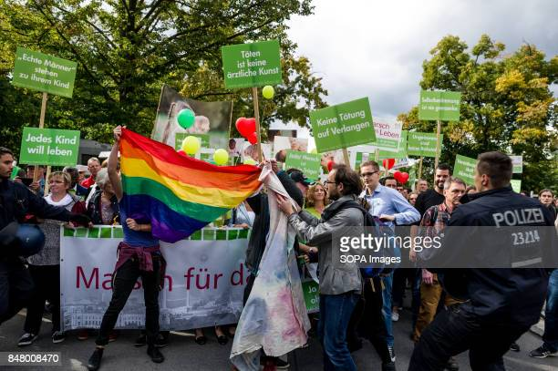Counterdemonstrators hold a rainbow flag in front of the demonstration Under the motto 'Protect the most vulnerable yes to every child'...