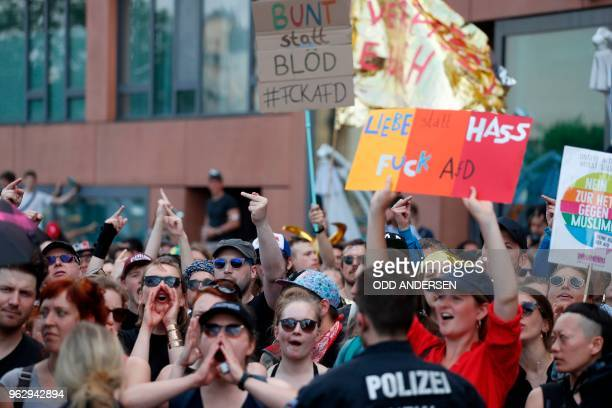Counterdemonstrators shot loud give their middle fingers and hold placards reading Colorful instead of idiot and Love instead of hate fuck AfD to...