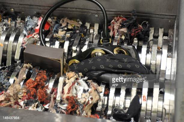 A counterfeit handbag seized by French customs is being destroyed in a special truck on May 29 2012 at the postal sorting center of Chilly Mazarin...