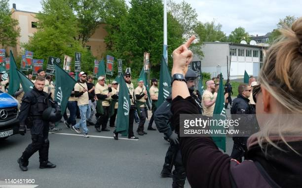 """Countermarcher shows her finger as supporters of the """"Der Dritte Weg/Der III Weg"""" far-right and neo-nazi party walk through Plauen, eastern Germany,..."""