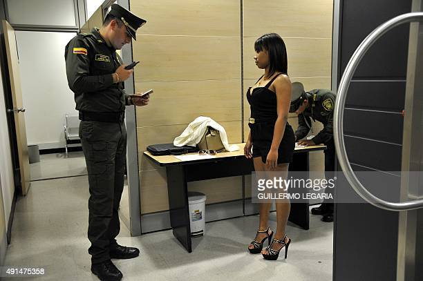 A counternarcotics policeman checks a woman's document before she goes through a body scanner at El Dorado international airport in Bogota Colombia...