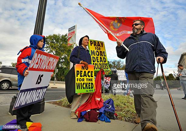 Counter-protester carrying a U.S. Marine Corps flag walks back and forth in front of protesters from the Westboro Baptist Church group, including...