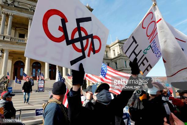 "Counter-protester displays placards during a ""Stop the Steal"" rally in support of US President Donald Trump at the Michigan State Capitol, on..."
