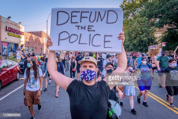 Counterprotester holding a Defund Police sign at the protest. Pro-NYPD marchers clashed with a big crowd of Black Lives Matter counterprotesters...