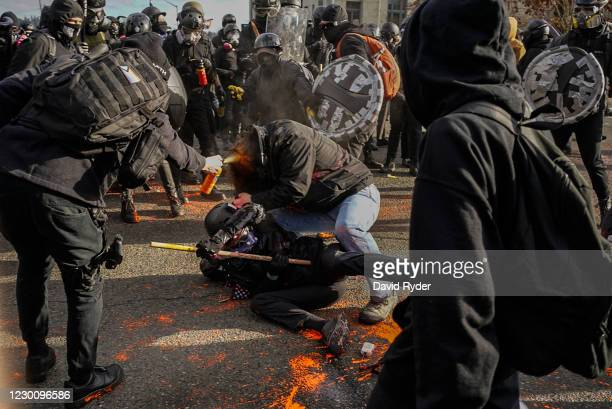 Counter-protester sprays a Trump supporter with bear mace during political clashes on December 12, 2020 in Olympia, Washington. Far-right and...