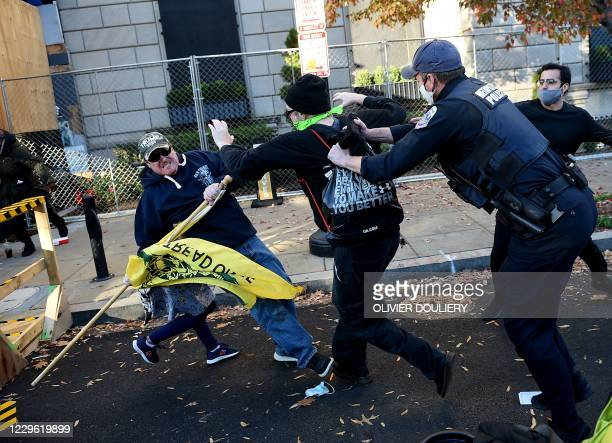 Counter-protesters clash with a supporter of US President Donald Trump as police intervene at Black Lives Matter Plaza during a rally in Washington,...