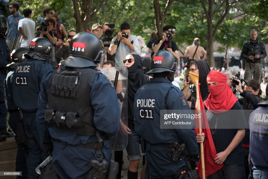 Counter-protesters confront police in Quebec City, Canada, on August 21, 2017. Clashes erupted Sunday between police and dozens of anti-racist activists on the sidelines of a pro-immigration rally in Quebec City while a demonstration organized by extreme-right activists gained little traction. In a bid to keep the two rallies apart, police erected a security cordon but declared the anti-racist demonstration illegal after sporadic clashes broke out and hooded individuals threw projectiles at police. PHOTO / Alice Chiche
