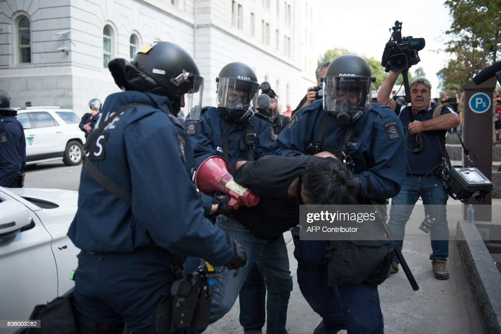 A counter-protesters is detained by police in Quebec City, Canada, on August 21, 2017. Clashes erupted Sunday between police and dozens of anti-racist activists on the sidelines of a pro-immigration rally in Quebec City while a demonstration organized by extreme-right activists gained little traction. In a bid to keep the two rallies apart, police erected a security cordon but declared the anti-racist demonstration illegal after sporadic clashes broke out and hooded individuals threw projectiles at police. PHOTO / Alice Chiche
