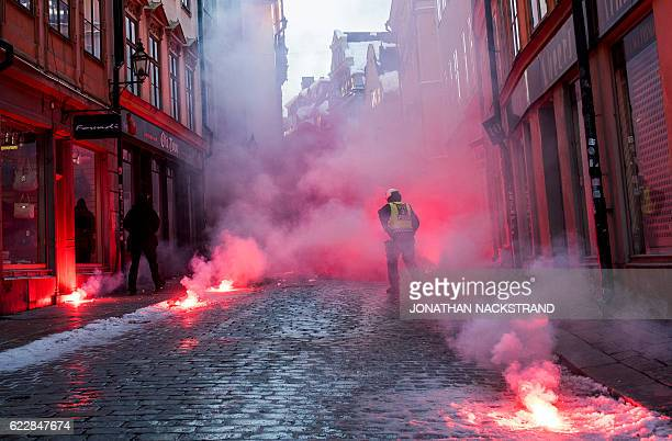 Counterprotesters throw flairs toward police officers as they demonstrate against the neonazi Nordic Resistance Movement rally in central Stockholm...