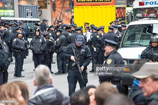 NYPD counterterrism officer checks his machine gun while standing guard near One Times Square With a heightened degree of security due to the threat...