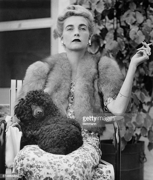 Countess HaugwitzReventlow is seated with a poodle in her lap as she watches a tennis match at Palm Beach Florida January 18 1940