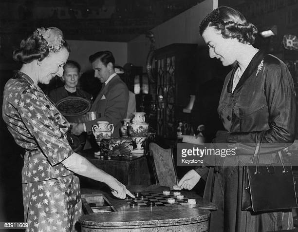 Countess Mountbatten of Burma opens the Antique Dealers' Fair at Grosvenor House, London, 8th June 1955. Here she plays chequers with her daughter...