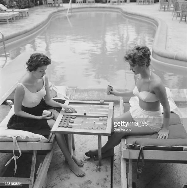 Countess Peter Jean-Baptiste de Manio and Mary-Beth Turner playing backgammon by a swimming pool in Palm Beach, Florida, 1959.