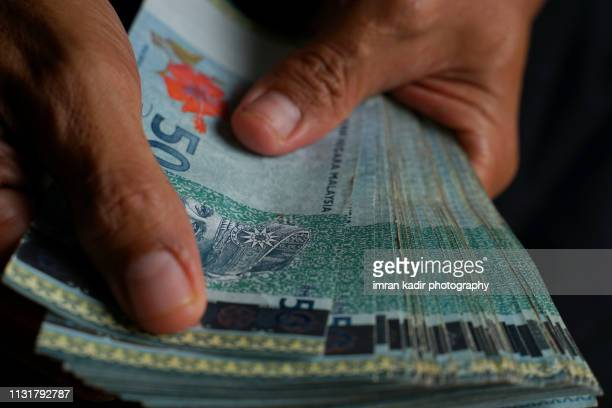 counting malaysian 50 ringgit in cropped hand - malaysian ringgit stock photos and pictures