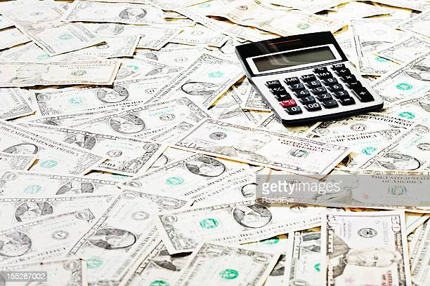 counting the cost: calculator on sea of dollar bills - bringing home the bacon stock photos and pictures