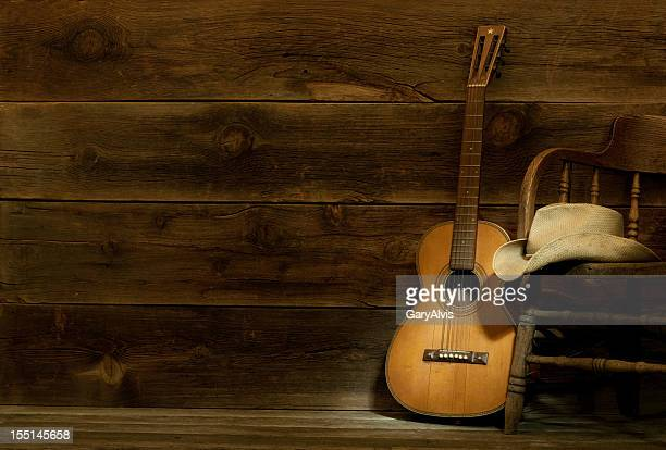 country and western music scene w/chair,hat,guitar-barnwood background - countrymusik bildbanksfoton och bilder