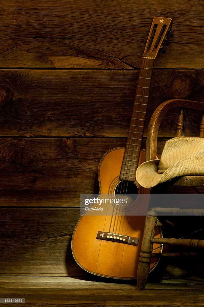 Country and Western scene w/ guitar,chair,cowboy hat-barnwood background : Stock Photo