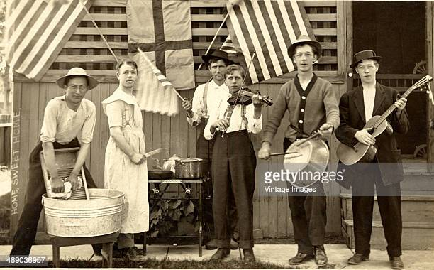 A country band with one man on washboard and another in drag USA circa 1910
