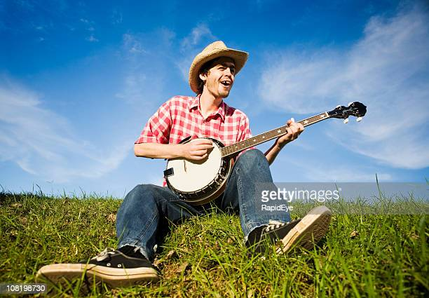 country boy plays the banjo in a rural summer meadow - banjo stock pictures, royalty-free photos & images