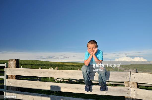 Country boy sits on fence in rural Alberta
