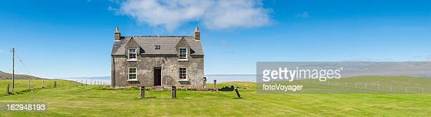Country cottage in vibrant green fields under blue summer skies