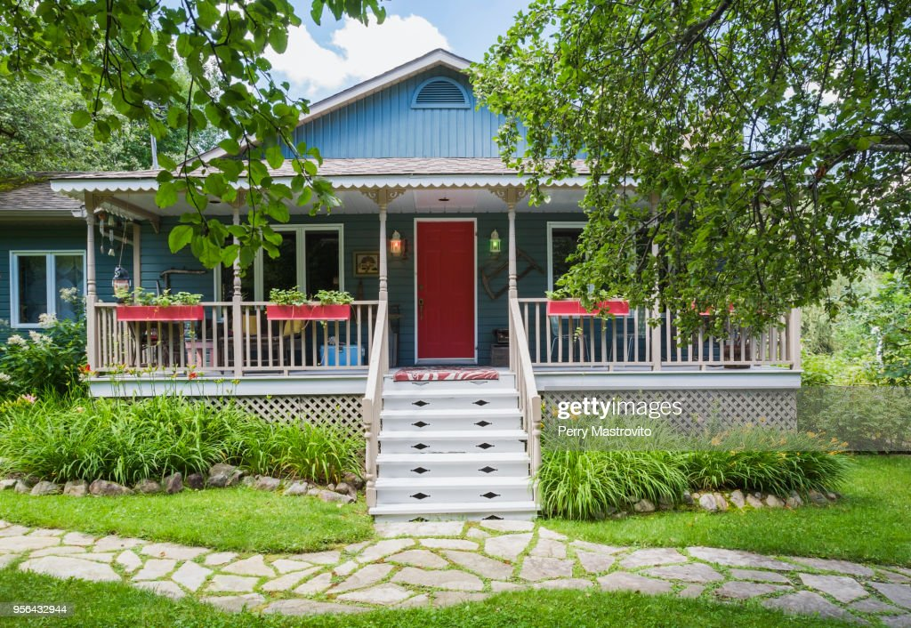 Country cottage style residential home facade with veranda in summer : Stock Photo