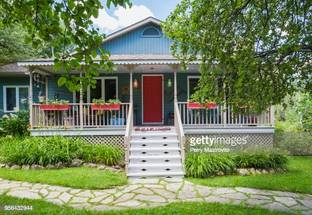country cottage style residential home facade with veranda in summer - facade stock pictures, royalty-free photos & images
