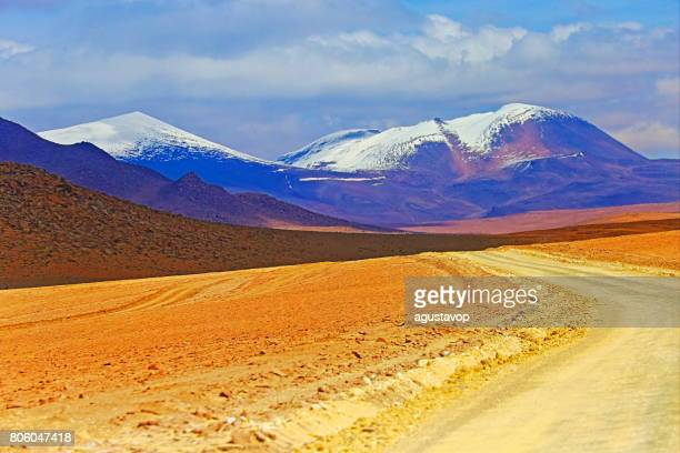 Country dirt road to Impressive Bolivian Andes altiplano and Idyllic Atacama Desert, Volcanic landscape panorama – Potosi region, Bolivian Andes, Chile, Bolívia and Argentina border