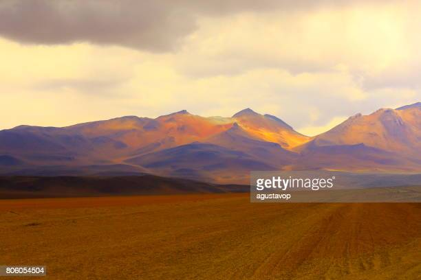 country dirt road to impressive bolivian andes altiplano and idyllic atacama desert, volcanic landscape panorama – potosi region, bolivian andes, chile, bolívia and argentina border - argentina stock pictures, royalty-free photos & images