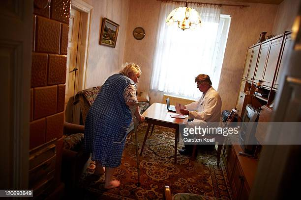Country doctor Dieter Baermann prepares the examining Emmy Guenther in the patient's home on August 8 2011 in Sachsendorf near Seelow Germany...