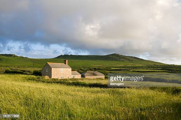 Country farm house in a grassy field near moorland