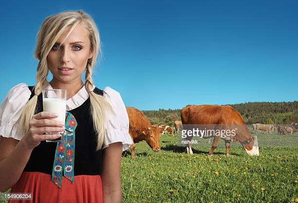 Fille de la campagne avec verre de lait et les vaches derrière