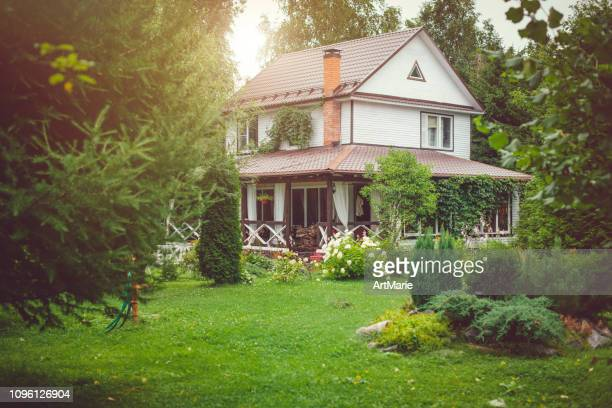 country house with green back yard in sunny summer day - house stock pictures, royalty-free photos & images