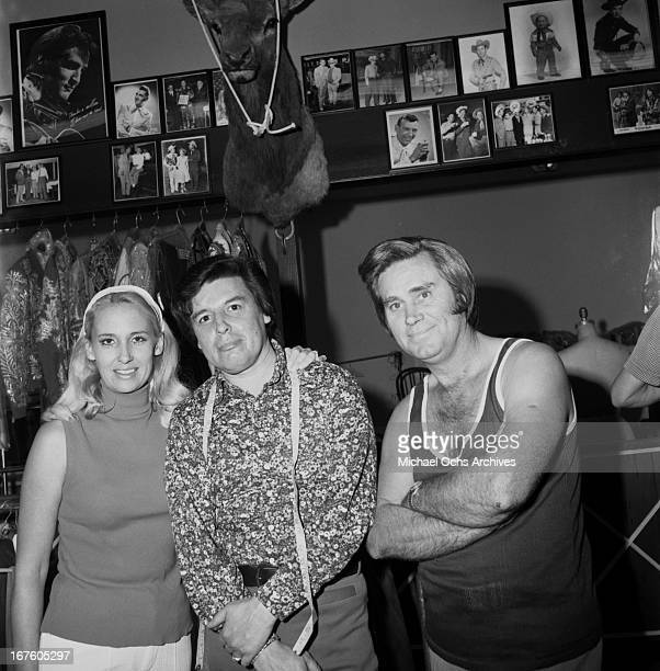 Country husband and wife singers Tammy Wynette and George Jones pose for a portrait with a tailor at Nudie's Rodeo Tailor on May 26 1973 in Los...