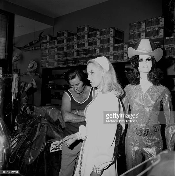 Country husband and wife singers Tammy Wynette and George Jones shop at Nudie's Rodeo Tailor on May 26 1973 in Los Angeles California