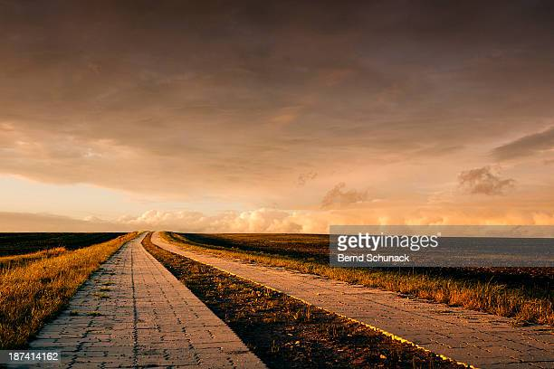 country lane leading to the horizon - bernd schunack stockfoto's en -beelden