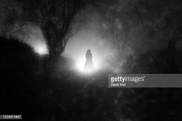 a country lane, on a foggy night with a ghostly woman in a dress. in front of glowing lights. with a grunge, blurred, vintage edit - fantasma fotografías e imágenes de stock
