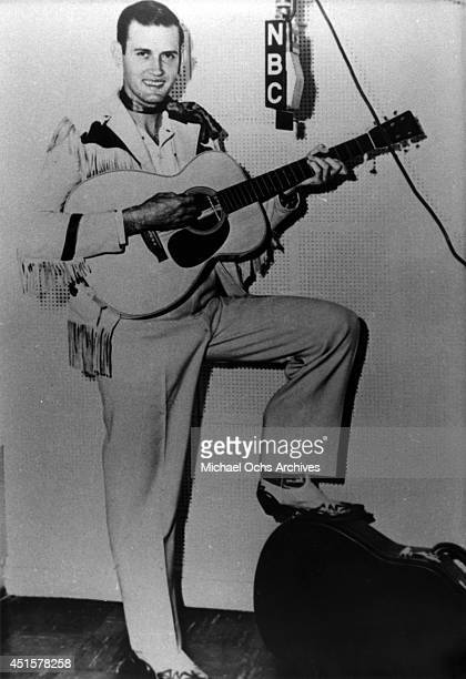 Country music and Grand Ole Opry star Jimmy C Newman poses for a portrait holding an acoustic guitar at a vintage NBC microphone in circa 1954 in...
