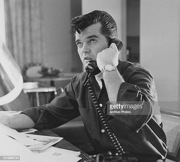 Country music singer and songwriter Conway Twitty talks on the telephone late 1950s or early 1960s
