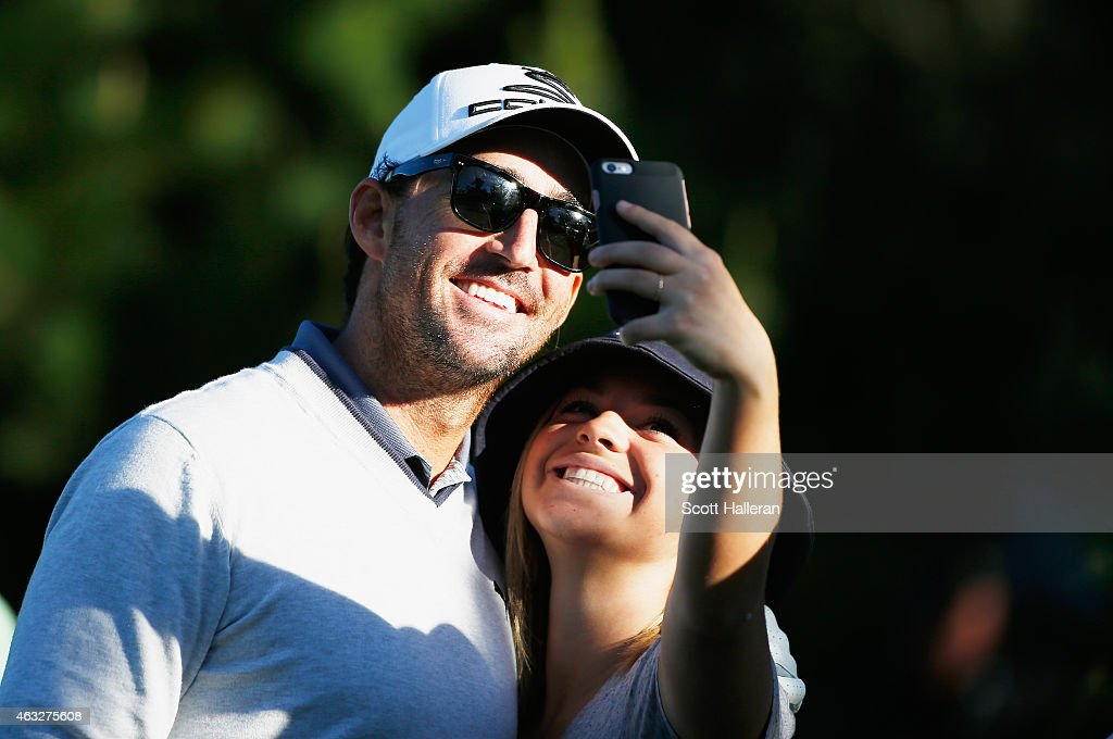 Country music star Jake Owen poses with a fan during the first round of the AT&T Pebble Beach National Pro-Am at Monterey Peninsula Country Club on February 12, 2015 in Pebble Beach, California.