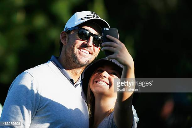 Country music star Jake Owen poses with a fan during the first round of the ATT Pebble Beach National ProAm at Monterey Peninsula Country Club on...