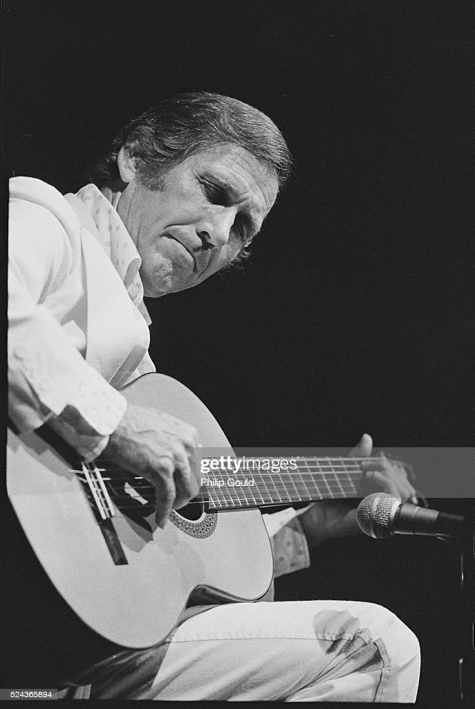 Country musician Chet Atkins sits on stage, playing his acoustic guitar.