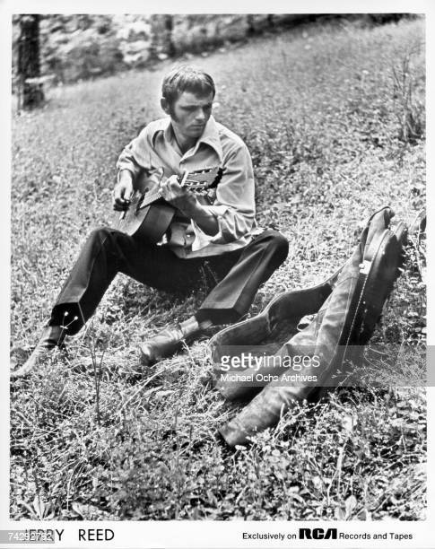 """Country musician Jerry Reed poses for a portrait playing acoustic guitar sitting on a grass field during a promotional session for the album """"Georgia..."""