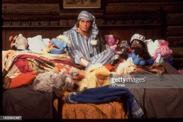 Country musician John Denver dressed in pyjamas and sitting in a bed full of puppets on the set of The Muppet Show at Elstree Studios, Hertfordshire,...