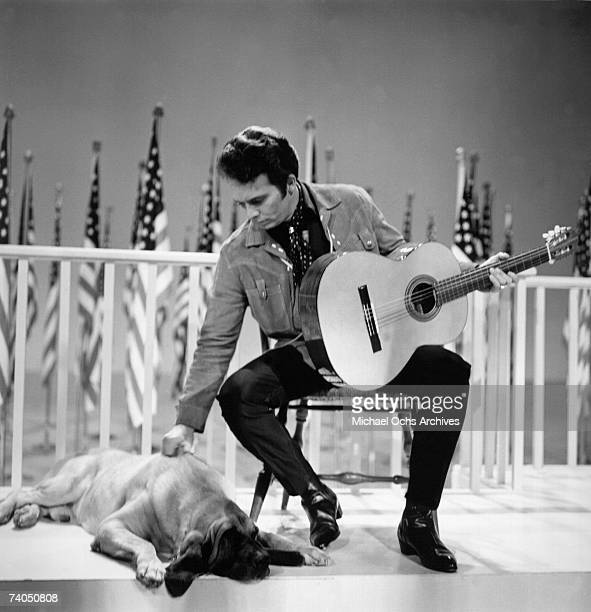 Country musician Merle Haggard performs on stage with a dog during a 1967 television show in Los Angeles California