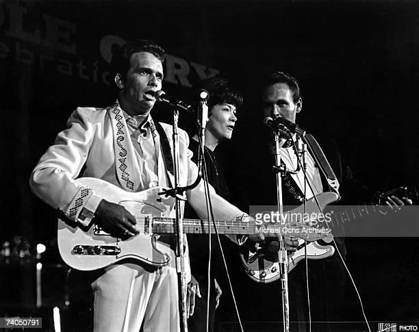 Country musician Merle Haggard performs on stage with singer Bonnie Owens and the bass player from his band Merle Haggard the Strangers during the...