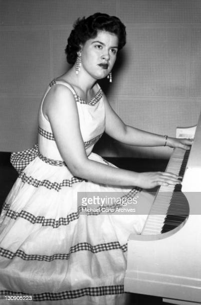 Country musician Patsy Cline plays the piano wearing a dress in circa 1957