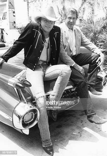 Country musicians Dwight Toakam and Buck Owens sitting on the hood of a 1959 Cadillac outside the Roosevelt Hotel Los Angeles July 29th 1988