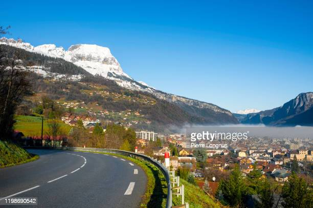 country road (route d1212) above the city of sallanches in morning mist, french alps in backdrop - sallanches stock pictures, royalty-free photos & images